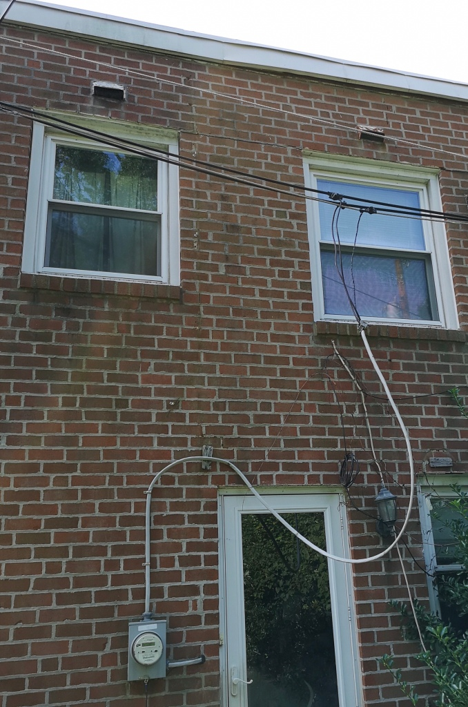 Wires hanging in front of a window and door, instead of neatly attached to the outside wall of the house.